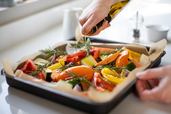 drizzling olive oil on pan of vegetables