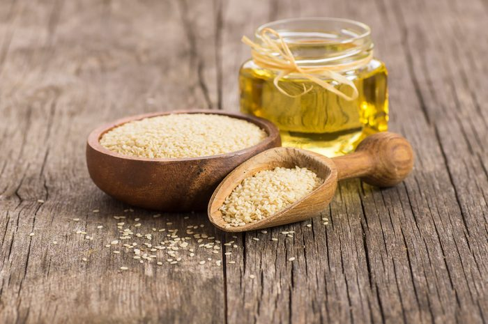 Glass bottle of sesame oil and raw sesame seeds