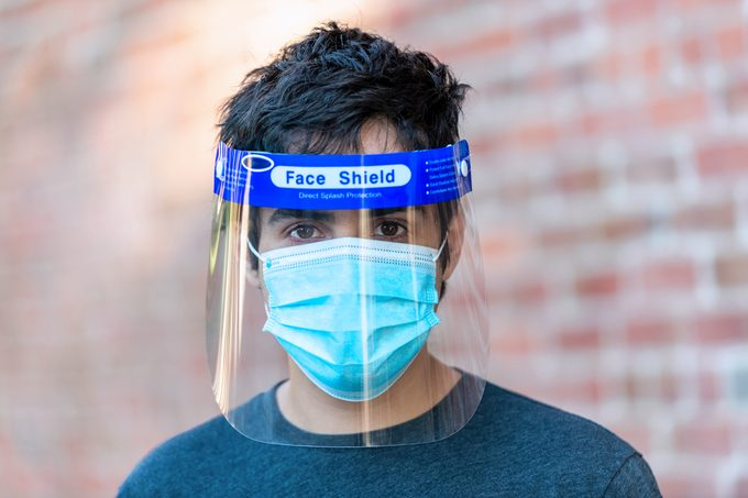 Young man wearing a face shield and a protective mask