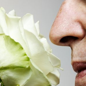 Senior man smelling rose, close-up