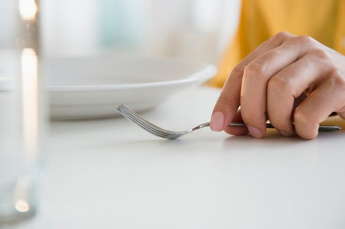 Close up of mixed race man holding fork at table