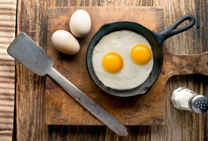 eggs in cast iron skillet on wood overhead