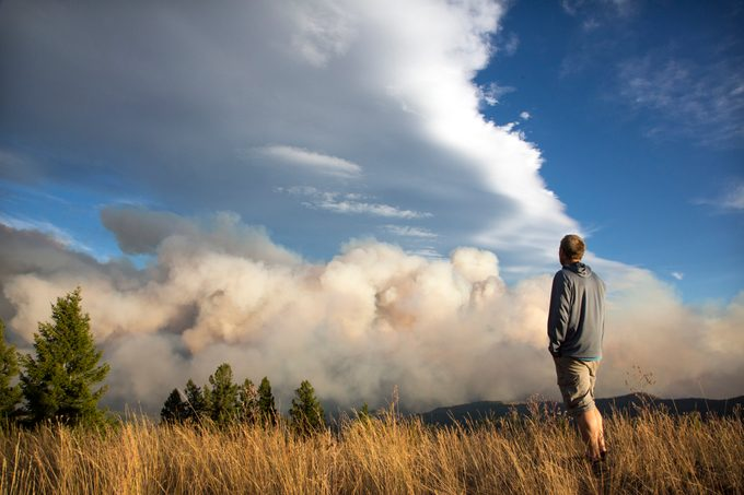 man in field looking at wildfire smoke