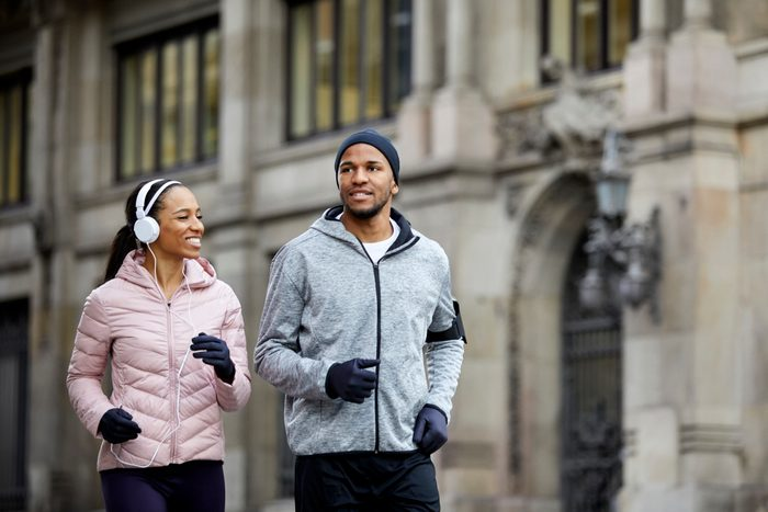 Smiling young couple talking while jogging in city