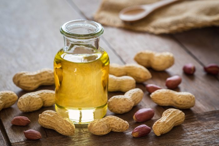 Peanut oil in glass bottle and peanuts