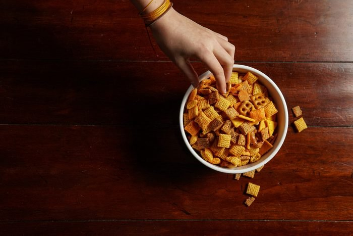 Hand reaching for bowl of junk food snacks - flat lay copy space