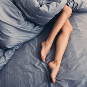 Part of female body on the bed