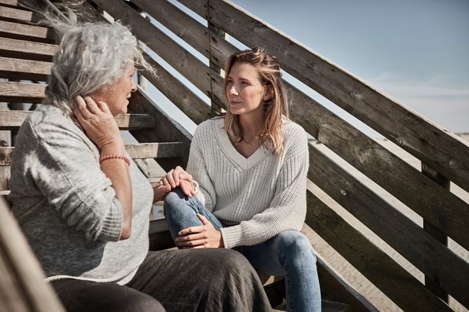 Senior woman talking with adult daughter on footbridge at the beach