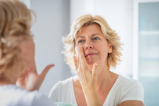 Mid adult woman spreading a layer of facial cream in front of the mirror