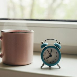 Pink cup of hot coffee with steam and retro alarm clock on window sill in morning