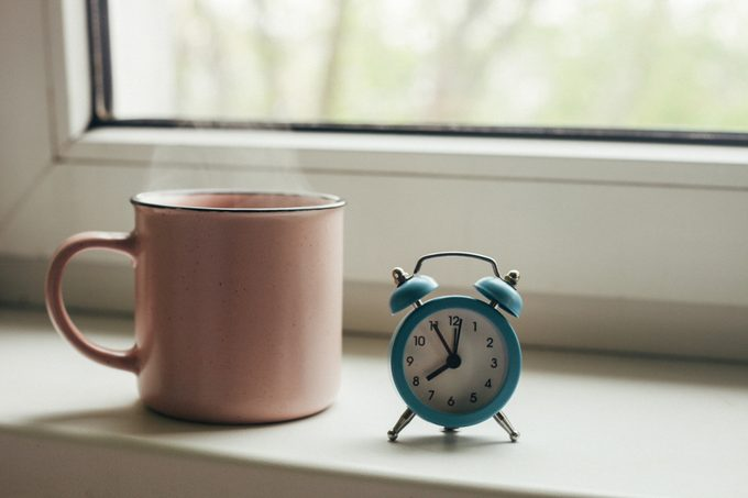 Pink cup of hot tea with steam and retro alarm clock on window sill