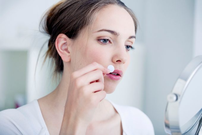 woman applying pimple patch to face
