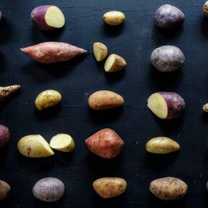 Closeup of fresh various organic potatoes on black background