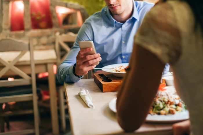 Man checking messages while having dinner in a restaurant