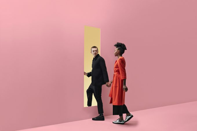Woman & man holding hands, approaching rectangular opening in colored wall