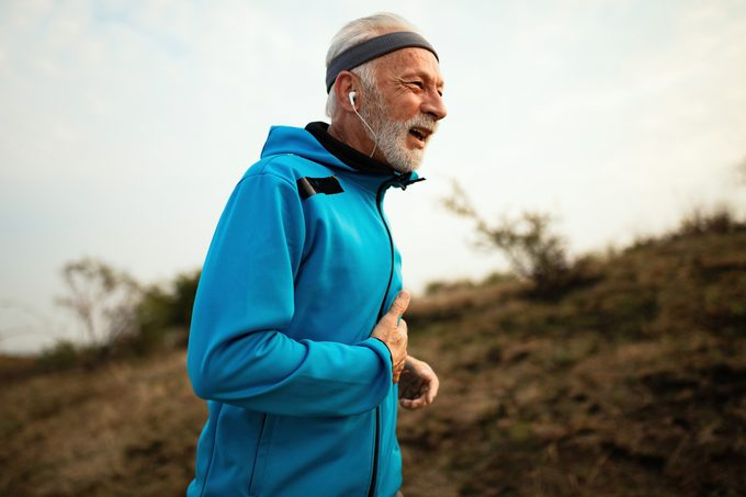 mature runner experiencing pain while jogging in nature