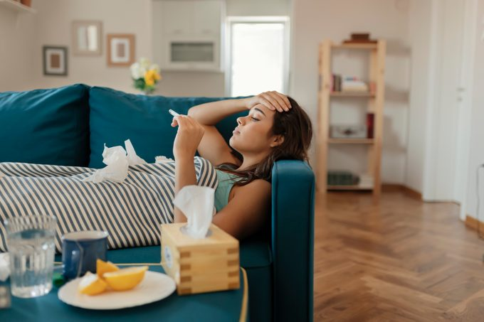 Woman on couch checking temperature