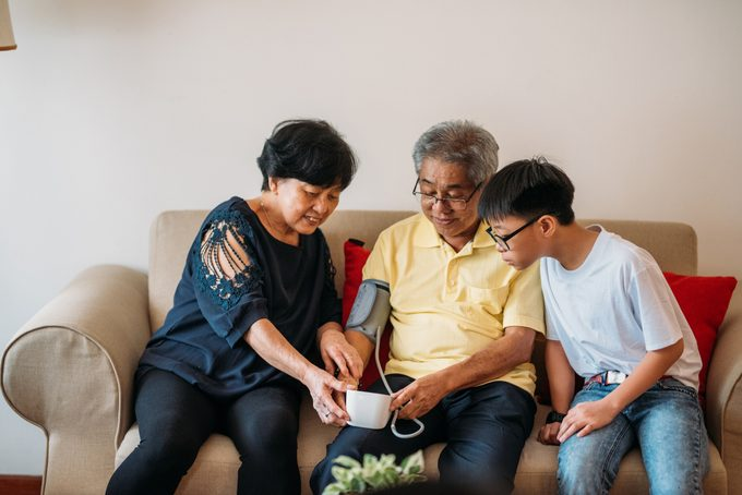 couple taking blood pressure with grandson