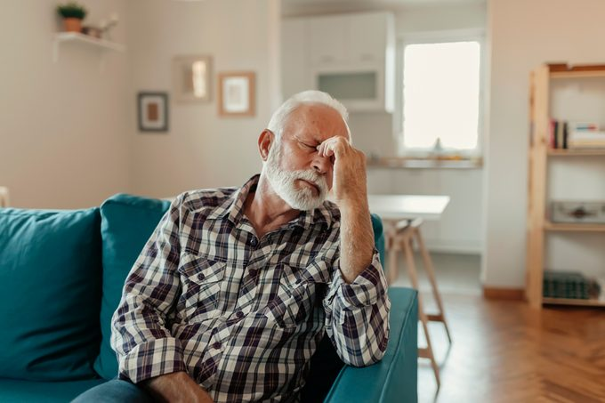 mature man with headache sitting on couch at home