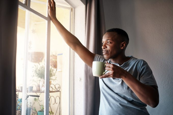 man looking out window with a cup of coffee