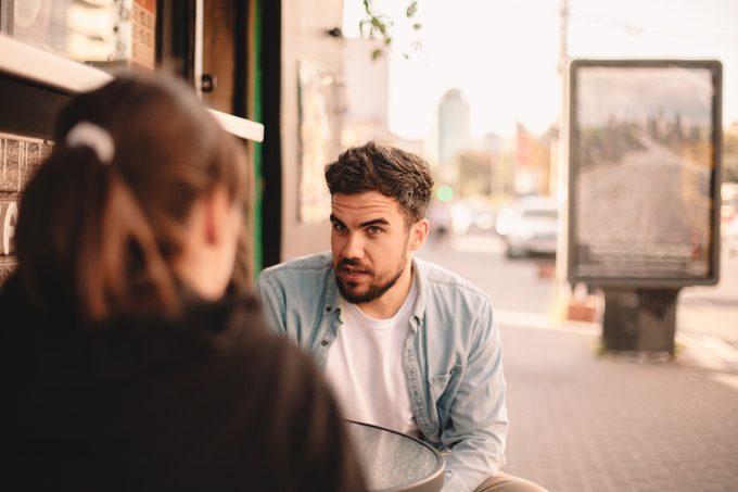 Couple talking while sitting at sidewalk cafe