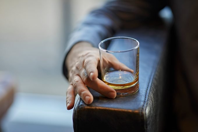 Close-up of man with whiskey glass on armrest of a leather chair