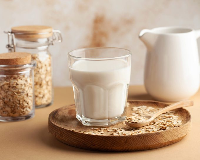 Oat milk in a glass, surrounded by jars of oats