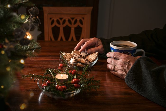 Hands of an elderly single man sitting alone at a table with Christmas cookies, coffee and festive decoration next to an empty chair, lonely holidays during the croronavirus pandemic or after a loss