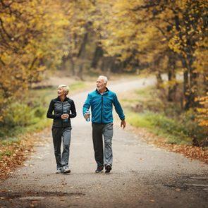Senior couple power walking in a park.