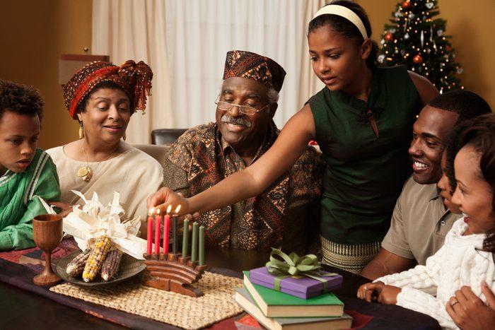Multi-generation family lighting Kwanzaa candles
