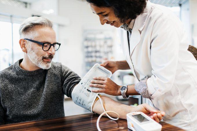 Pharmacist Measuring Man's Blood Pressure