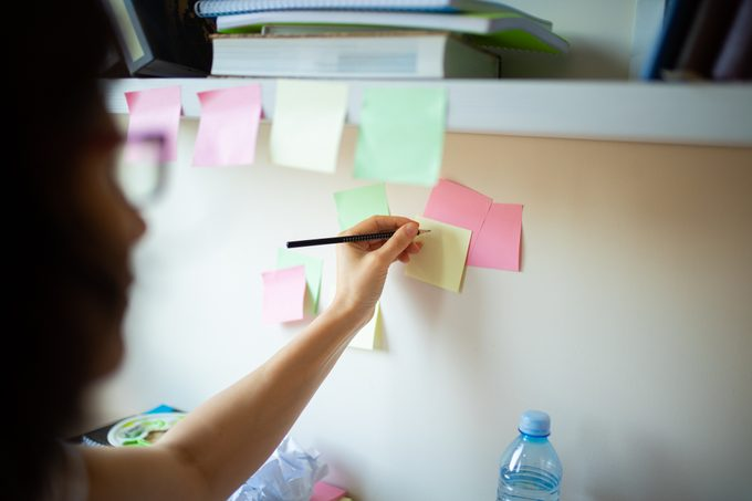 woman writing on post-it notes on the wall