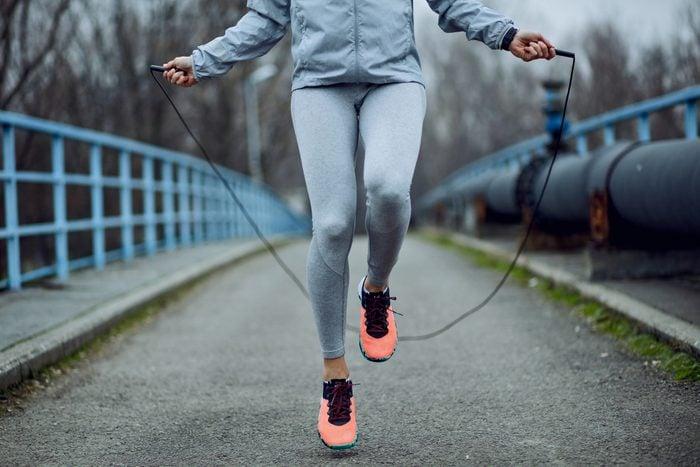 Unrecognizable sportswoman jumping rope on a bridge.