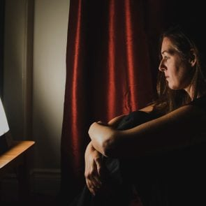Profile of woman sitting looking at light therapy lamp in a dark room