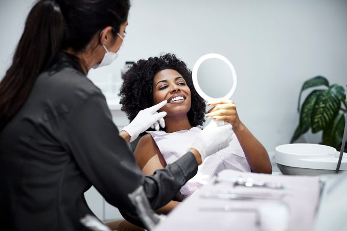 Patient looking teeth in mirror at dental clinic
