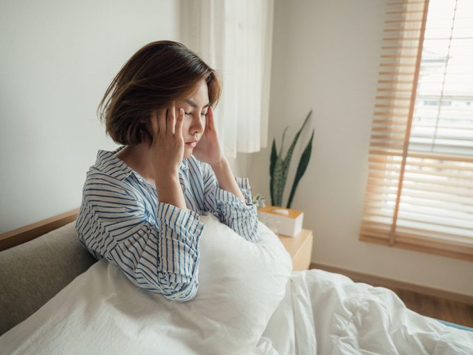 Asian woman caught flu and drinking water in bed at home.