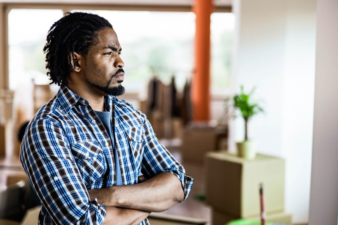 Serious black man with crossed arms in his new home.