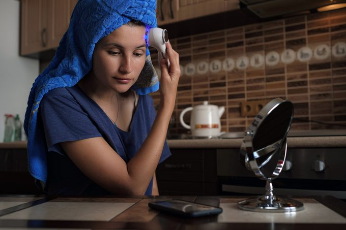 A woman is sitting in the kitchen and doing a beauty procedure using a beauty gadget.