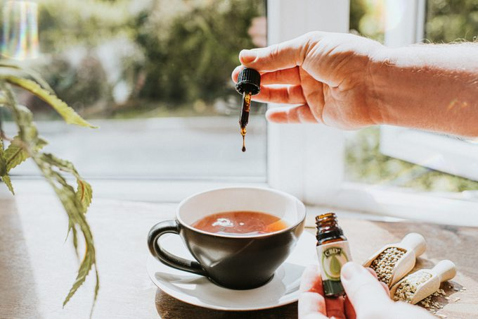 Hand dropping CBD oil into a Cup of Tea, surrounded by Cannabis Plants