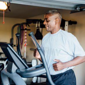 Black man running on treadmill in garage