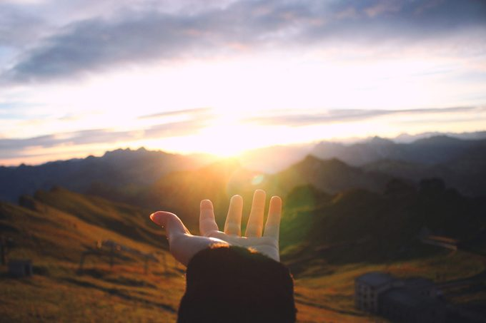 Hand Outstretched Towards Scenic View Of Mountains
