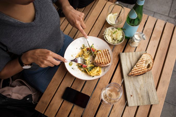 High angle view of woman having lunch at sidewalk cafe table