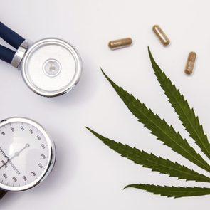 marijuana leaf and blood pressure monitor on white background
