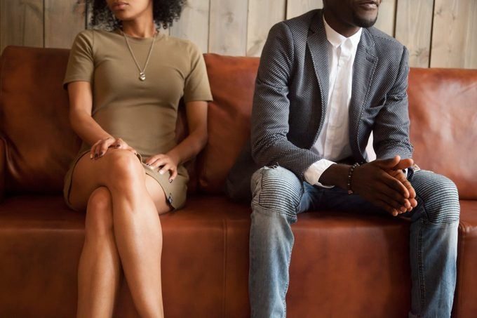 African-american couple sitting on couch after quarrel, bad relationships concept