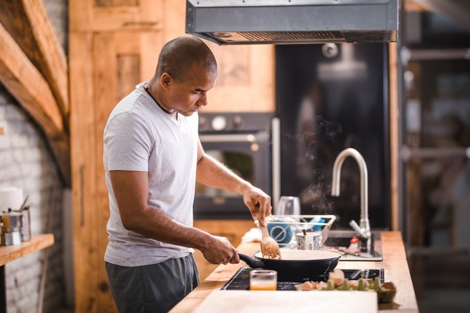 man preparing scrambled eggs for breakfast.