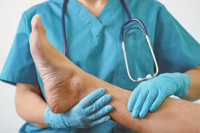 The doctor's hands in gloves hold a foot with toe, infected with nail fungus for examination and diagnosis.