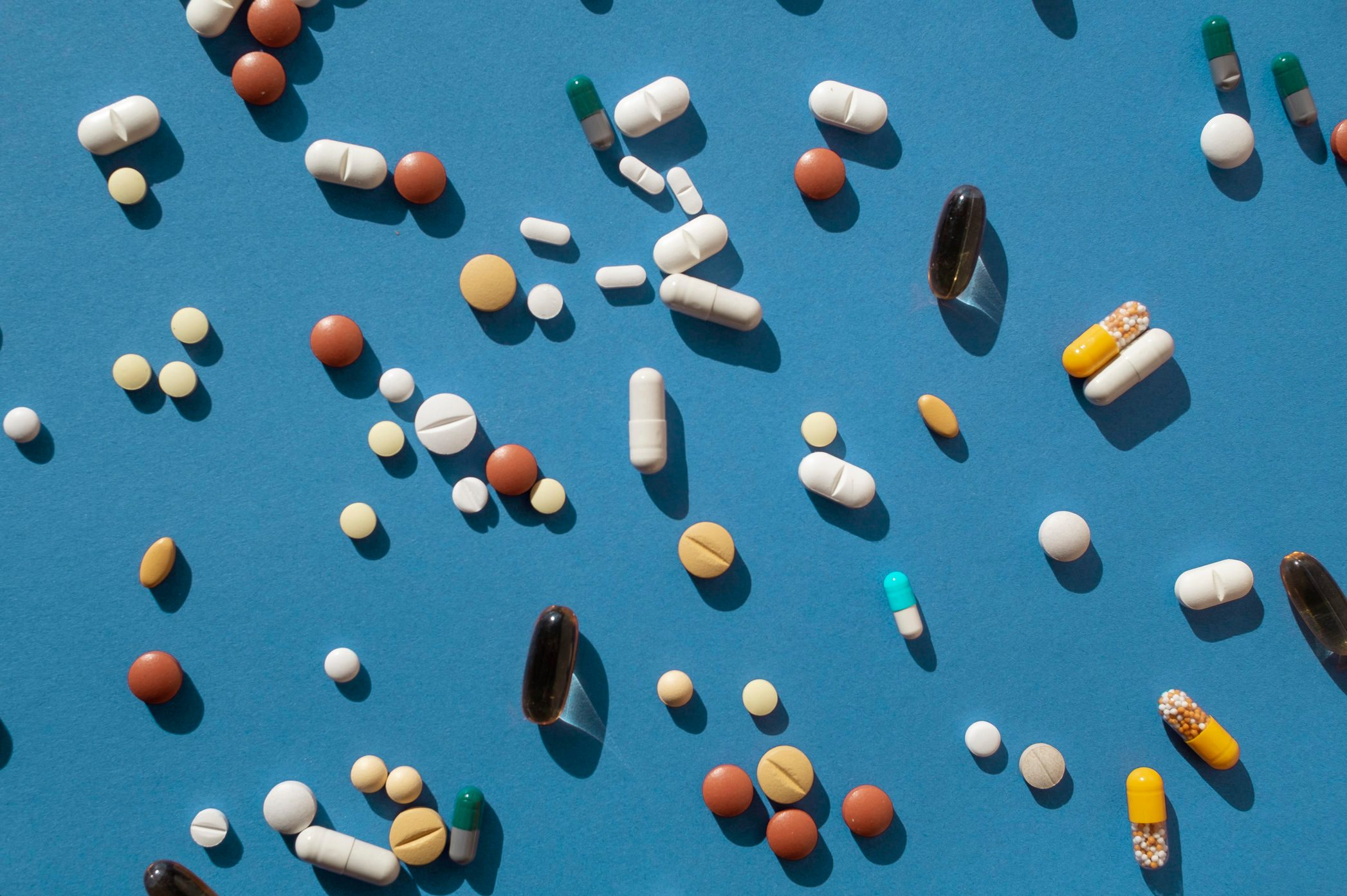 Top view of various pills and tablets on the blue background