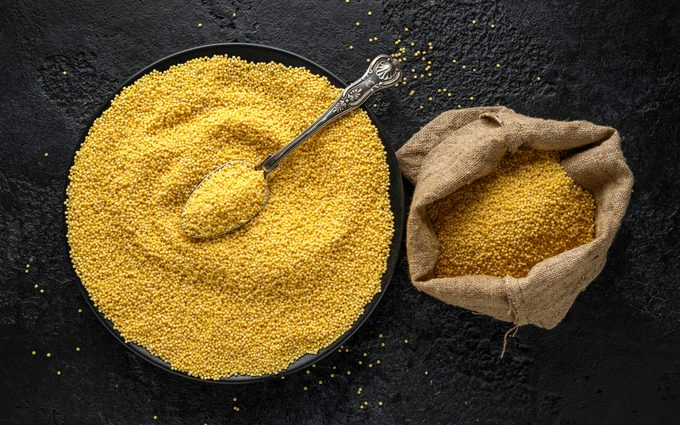 Millet cereal grains pouring in burlap sack, bag. Organic concept