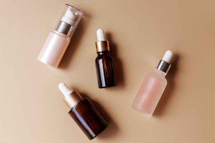 Set of amber glass cosmetic bottles on brown background. Pump bottle, dropper bottle, dispenser cosmetic container Flat lay, top view.