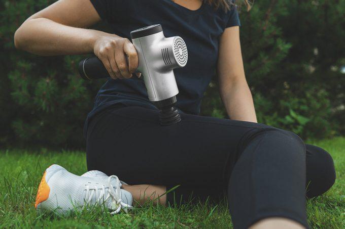 Woman massaging leg with massage percussion device